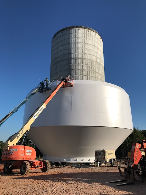 Tower bowl is on ground while contractors are painting it.